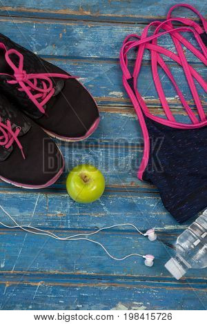 Overhead view of womenswear with Granny Smith apple and bottle by headphones on wooden table