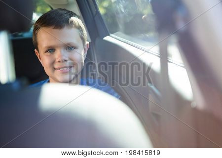 Portrait of happy teenage boy sitting in the back seat of car