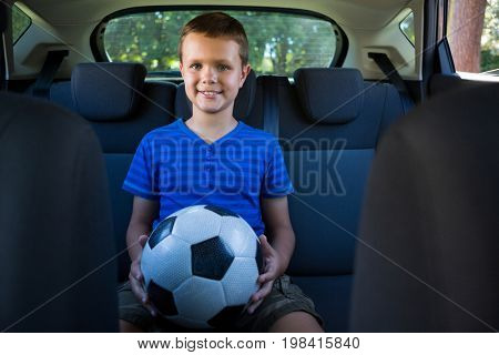 Portrait of happy teenage boy sitting with football in the back seat of car
