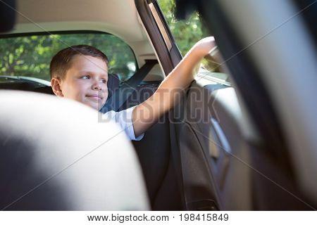 Happy teenage boy sitting in the back seat of car