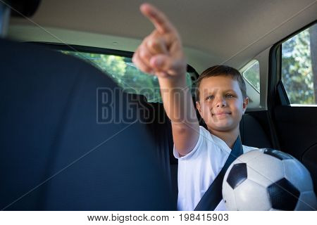 Smiling teenage boy pointing while sitting in the back seat of car