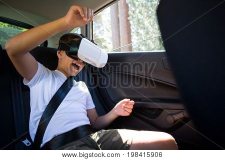 Teenage boy using virtual reality headset in the back seat of car