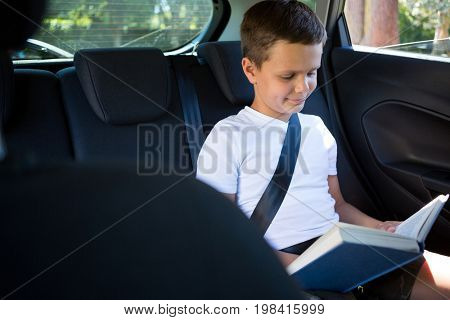 Smiling teenage boy reading book in the back seat of car
