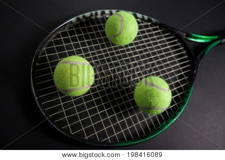 High angle view of fluorescent yellow tennis racket and balls against black background