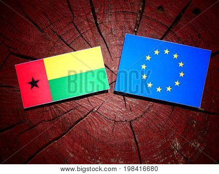 Guinea Bissau Flag With Eu Flag On A Tree Stump Isolated