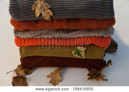 Stack of woolen clothing with autumn leaves on white background