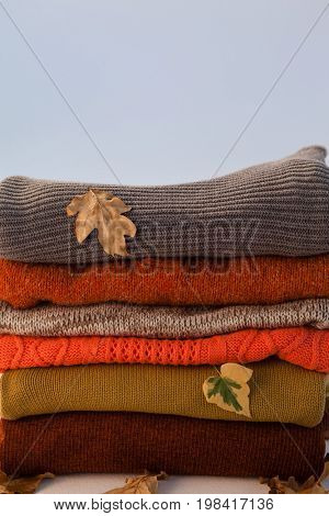 Stack of woolen clothing with autumn leaves against white background