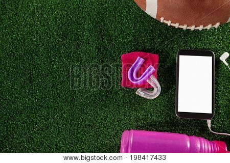 Close up of smart phone by American football on field