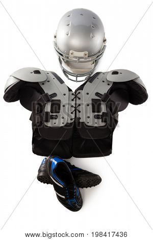 Overhead view of chest protector with sports helmet and shoes against white background