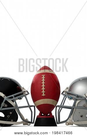 American football on tee by silver and black sports helmets against white baclground