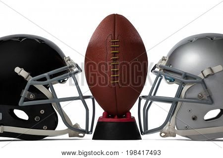 Close up of brown American football on tee by sports helmets against white baclground