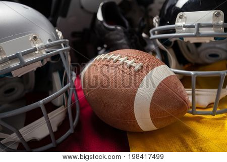 Close up of brown American football with helmets on jersey