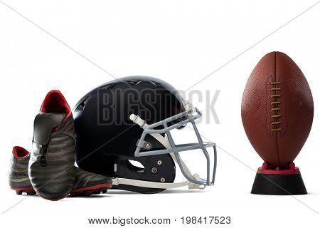 Close up of sports shoes and helmet by American football on tee against white background