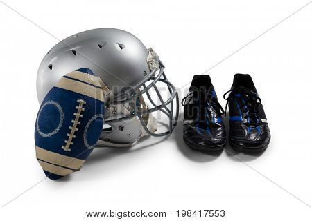 High angle view of American football with sports shoes and helmet against white background