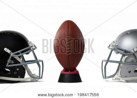 American football on tee by sports helmets against white baclground