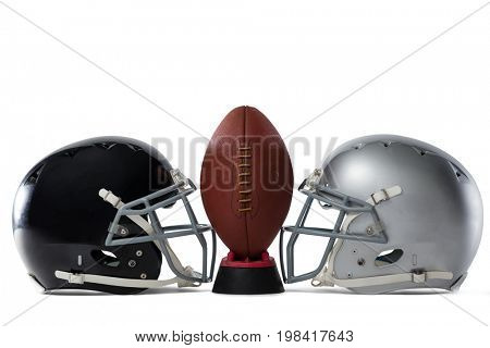 Close up of American football on tee by sports helmets against white baclground