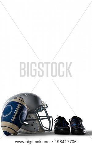 American football with sports shoes and helmet against white background