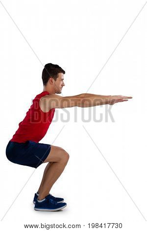 Side view of sports player exercising with arms outstretched while bending against white background