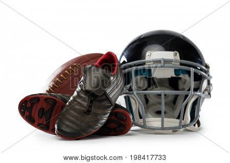 Close up of sports shoes with helmet and American football against white background