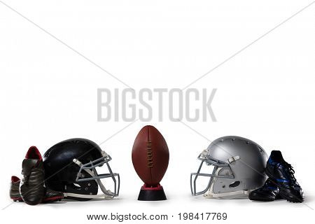 American football on tee by sports shoes and helmets against white background