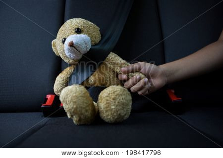 Close-up of teenage girl sitting with teddy bear in the back seat of car