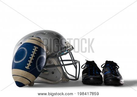 Close up of America football and helmet by sports shoes on white background