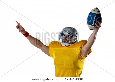 Happy American football player holding ball while standing with arms outstretched against white background