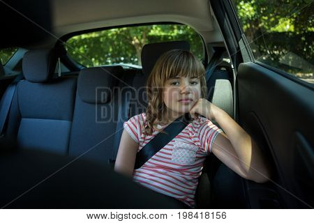 Portrait of teenage girl sitting in the back seat of car