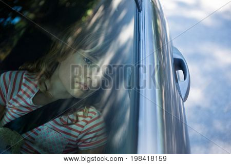 Thoughtful teenage girl with teddy bear sitting in the back seat of car