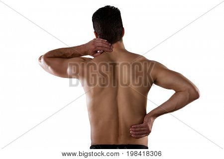 Rear view of shirtless sportsperson suffering from pain while standing against white background