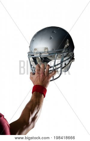 Cropped image of hand wearing wristband holding helmet against white background