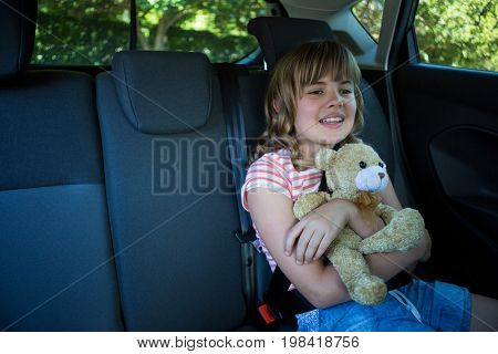 Happy teenage girl with teddy bear sitting in the back seat of car