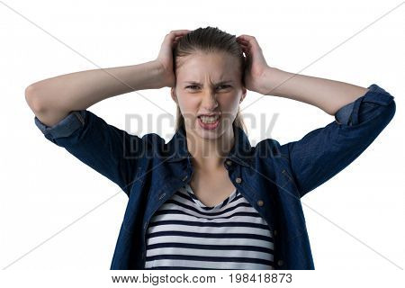 Portrait of frustrated teenage girl scratching her head against white background