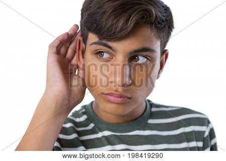 Teenage boy listening secretly with hands behind her ears against white background