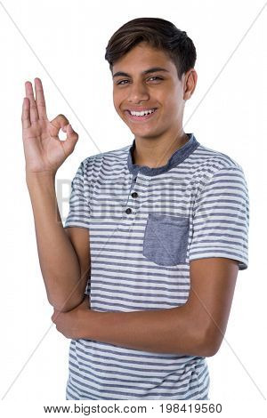 Smiling teenage boy gesturing okay hand sign against white background