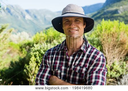 Portrait of smiling farmer standing with arms crossed in farm