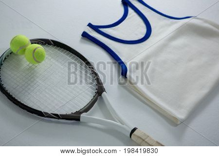 High angle view of racket with tennis balls by vest on white background
