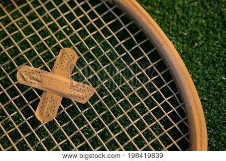 Cropped image of racket with bandage on field