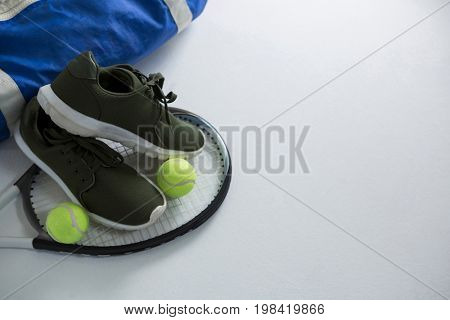 Sports shoe and tennis balls on racket by bag over white background