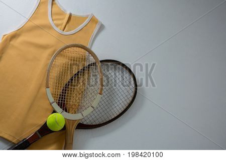 Directly above shot of rackets with vest and tennis ball on white background