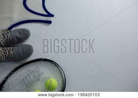 Cropped image of racket with ball and sports shoe by vest on white background