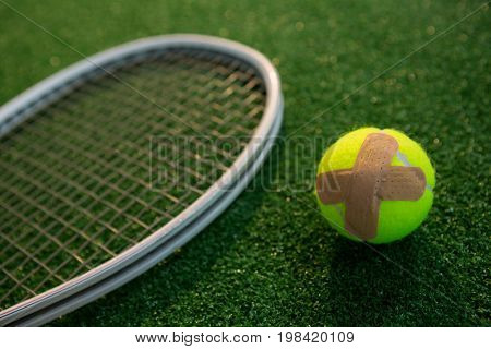 Close up of tennis ball with bandage by racket on field