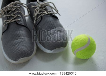 Close up of sports shoes with tennis ball on white background