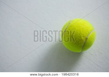 Overhead view of fluorescent tennis ball on white background