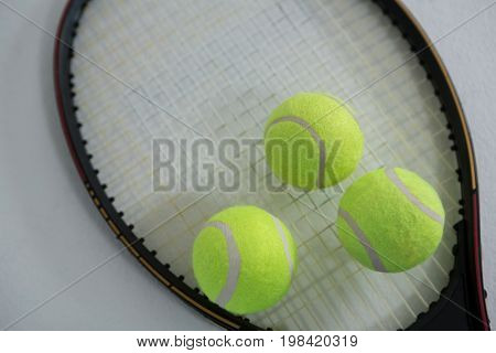 Close up of fluorescent yellow tennis ball on racket against white background