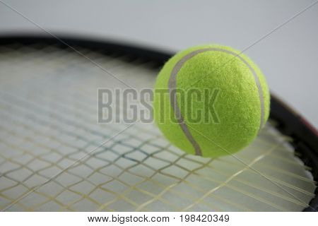 Close up of fluorescent tennis ball on racket against white background