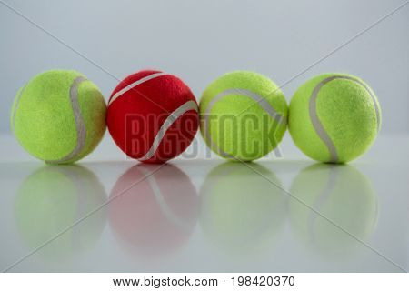 Red and fluorescent tennis ball on white background