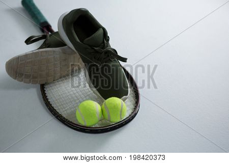 High angle view of sports shoe with tennis ball and racket on white background