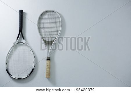 Overhead view of metallic tennis rackets on white background