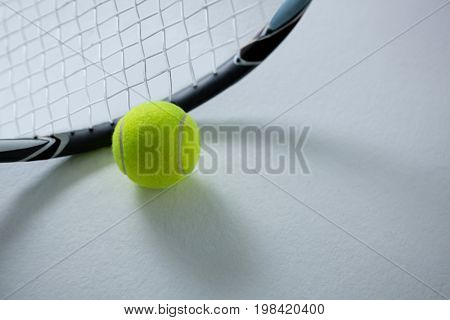 Cropped image of racket with ball on white background